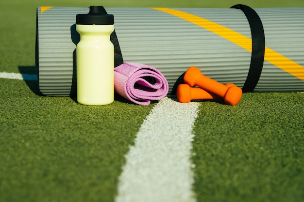 Op de achtergrond van kunstgras is er een mat, een fles, een fitness elastische band en een mat. sportuitrusting.