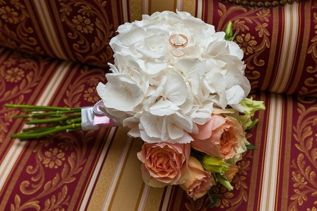 Op de barokke bank ligt een bruidsboeket rozen. boeket rozen, bruiloft bloemen.
