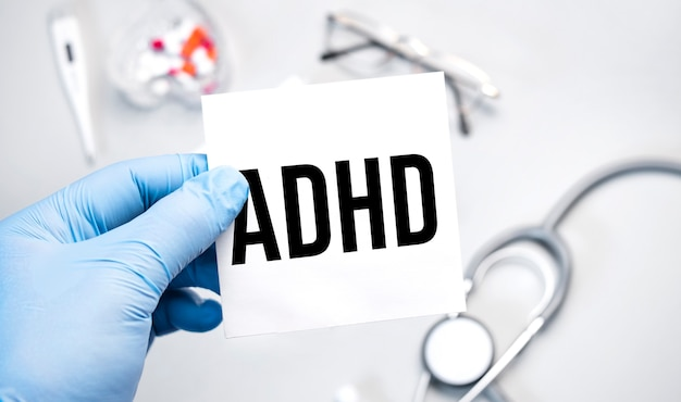Op de blauwe gehandschoende handen van de dokter staat het woord adhd -. een gehandschoende hand op een witte achtergrond.