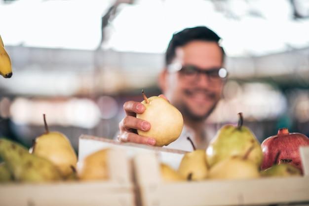 Op de boerenmarkt, focus je op het fruit op de voorgrond.