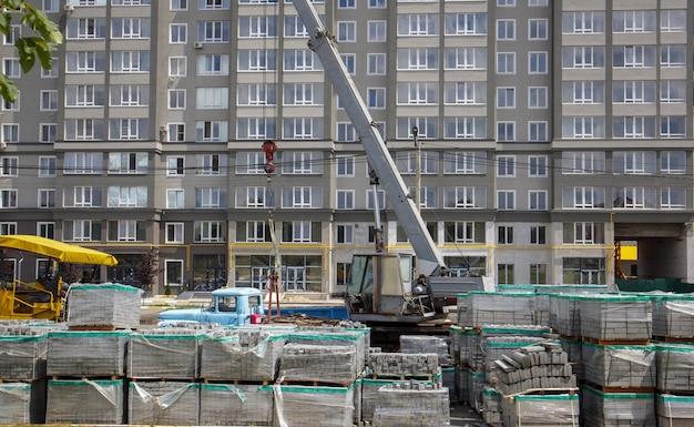 Op de bouwplaats liggen veel nieuwe grijze straatplaten op met kunststof omhulde pallets. bestrating van voetpaden op een stadsstraat. voorgrond. reparatie van de stoep op het stadsplein.