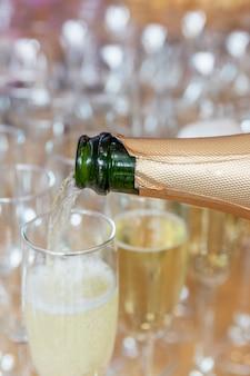 Op de buffettafel wordt champagne in een glas gegoten. detailopname. verticaal.