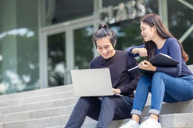 Op de campus gebruikt een prachtig stel in casual kleding een laptop terwijl ze op het buitentrappenhuis zitten.