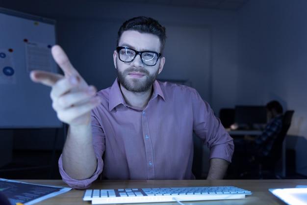 Op de computer. vrolijke positieve bebaarde man zit aan de tafel en op zoek naar jou tijdens het werken op de computer