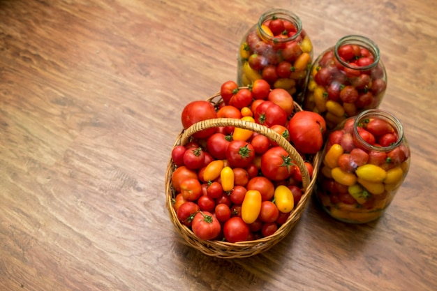Op de foto staat een mand met tomaten. vers biologisch voedsel uit eigen tuin. op de achtergrond staan potten met conserven voor de winter.
