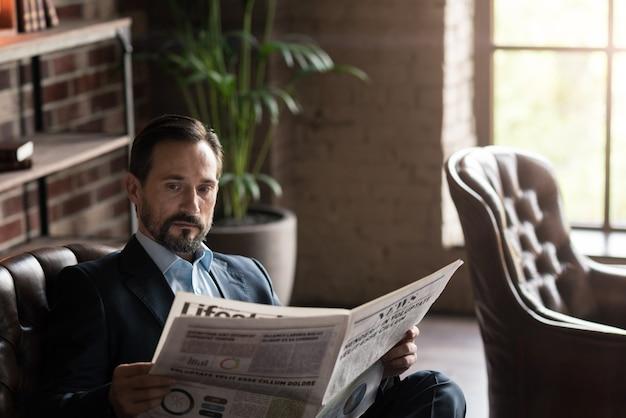 Op de hoogte zijn. aangename knappe aantrekkelijke man die een krant vasthoudt en het laatste nieuws leest terwijl hij op kantoor is