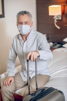 Op de hotelkamer. grijsharige man van middelbare leeftijd met een beschermend masker in een hotelkamer