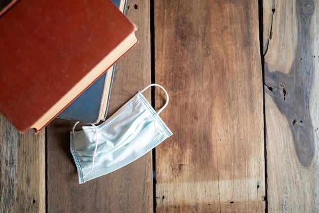 Op de houten tafel worden boeken en hygiënemaskers gelegd.