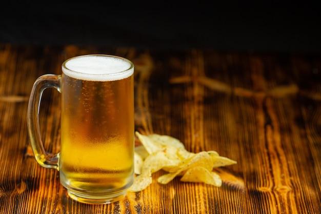 Op de houten vloer staat een glas bier.