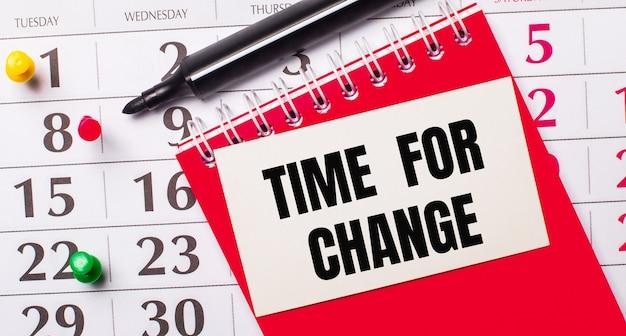 Op de kalender staat een witte kaart met de tekst time for change. in de buurt is een rode blocnote en een marker. uitzicht van boven