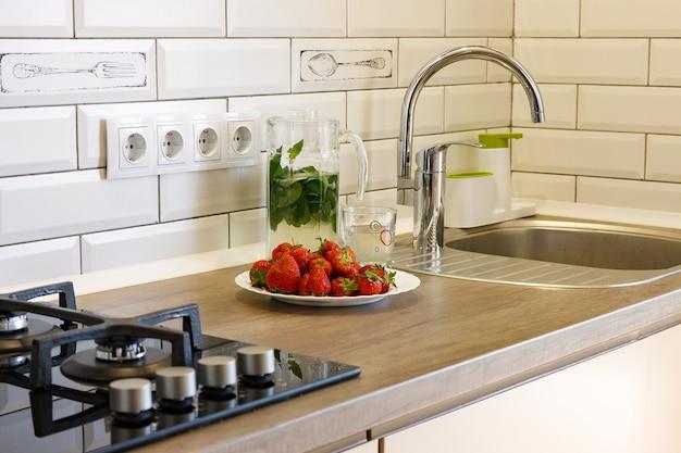 Op de keukentafel staat een bord met aardbeien en een kan water en munt.