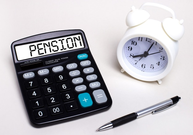 Op de lichttafel ligt een zwarte rekenmachine met de tekst pension op het scorebord, een pen en een witte wekker. bedrijfsconcept