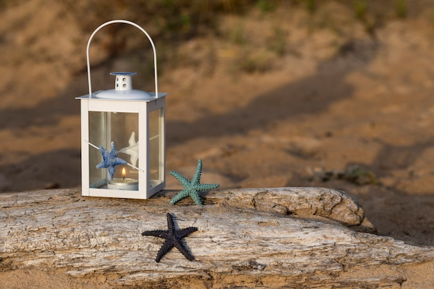 Op de oude balk in een lantaarn in nautische stijl en twee zeesterren in het zand