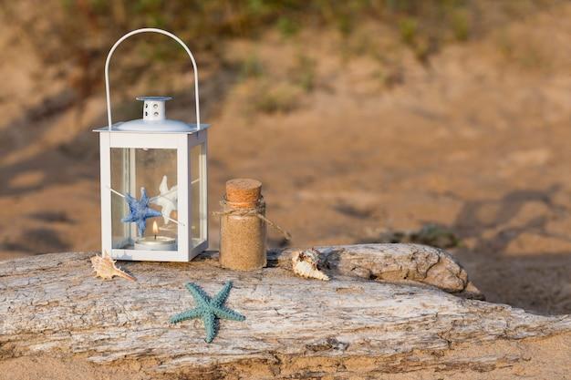 Op de oude balk in een nautische lantaarn, schelpen, een fles zand en een zeester in het zand