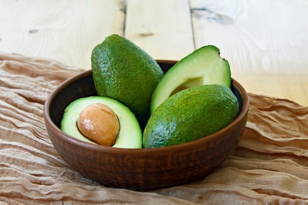 Op de plaat zijn avocado's op een houten achtergrond