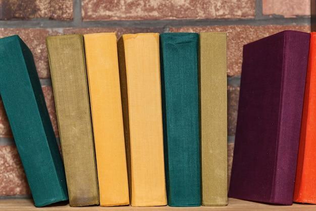 Op de planken staat een rij oude boeken met veelkleurige omslagen