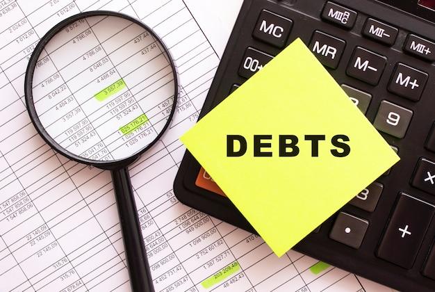 Op de rekenmachine ligt een gekleurde sticker met de tekst. financieel concept.