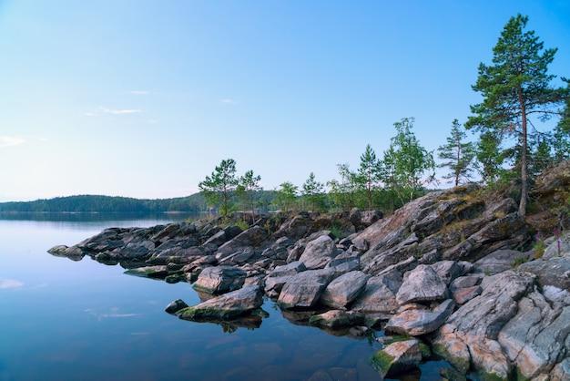 Op de rotsachtige kust van het eiland aan het meer