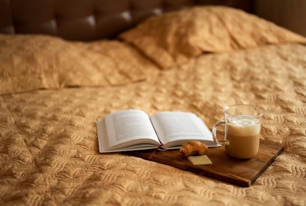 Op de sprei staan een boek en koffie.