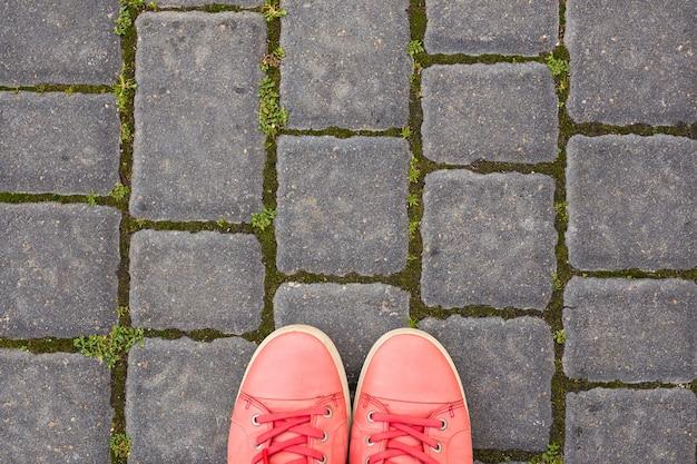 Op de straatstenen staan rode gympen, bovenaanzicht