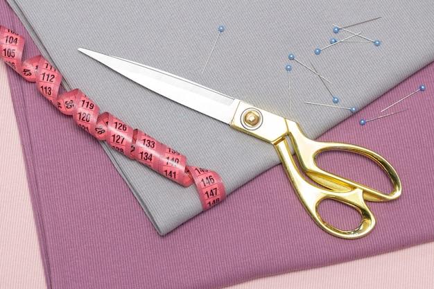 Op de strelingen van de stof liggen een schaar en een meetlint. naaien hobby concept. winkel atelier.