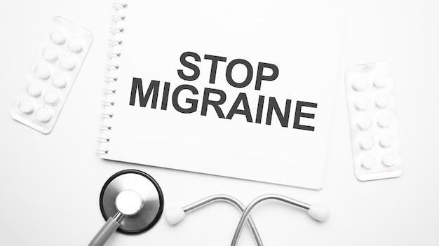 Op de tablet voor het schrijven van de tekst stop migraine, naast de stethoscoop en witte tabletten.