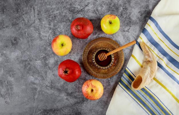 Op de tafel in de synagoge staan de symbolen van rosh hashanah-appel en granaatappel, shofar talith