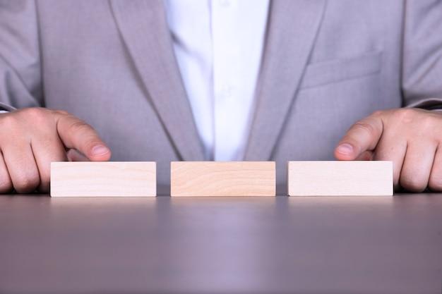 Op de tafel liggen drie houten blokken tegen de achtergrond van een zakenman.