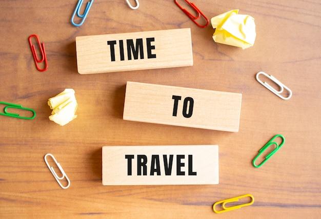 Op de tafel liggen houten blokken verspreid. tijd voor reizen staat op de blokken geschreven.