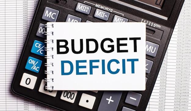 Op de tafel liggen rapporten, een rekenmachine en een kaart met de woorden budget deficit erop