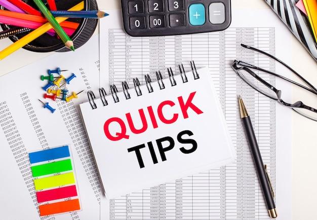 Op de tafel liggen rapporten, een rekenmachine, kleurpotloden en stickers, een pen en een notitieboekje met de tekst snelle tips