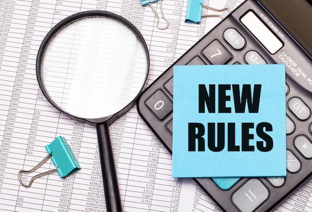 Op de tafel liggen rapporten, een vergrootglas, een rekenmachine en een blauwe notitie-sticker met de woorden nieuwe regels. bedrijfsconcept