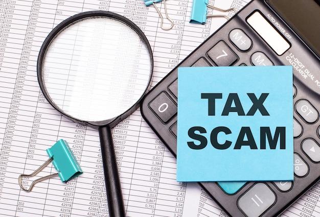 Op de tafel liggen rapporten, een vergrootglas, een rekenmachine en een blauwe notitie-sticker met het woord tax scam. bedrijfsconcept