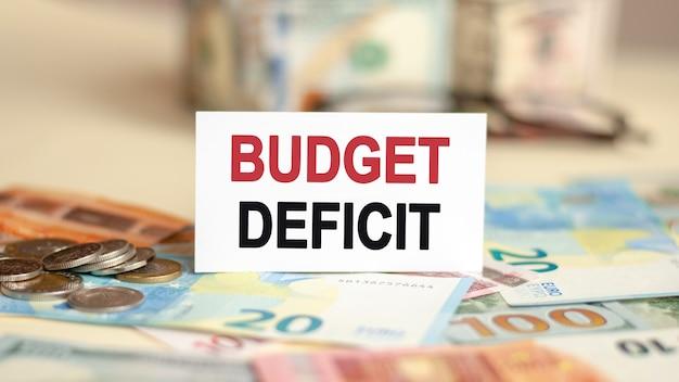Op de tafel liggen rekeningen, een bundel dollars en een bord waarop het is geschreven - budget deficit
