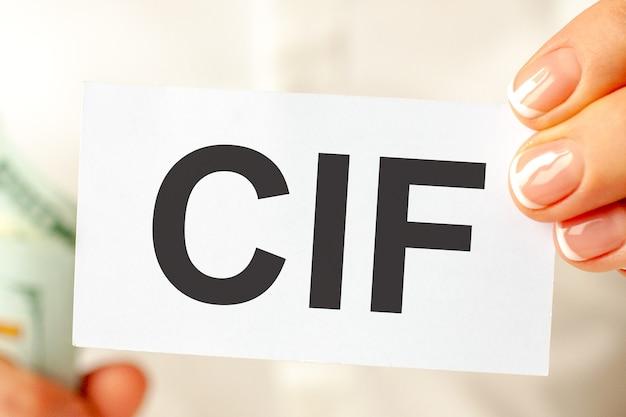 Op de tafel liggen rekeningen, een bundel dollars en een bord waarop het is geschreven - cif. cif afkorting voor custom factory integration. zaken, financiën en economie concept.