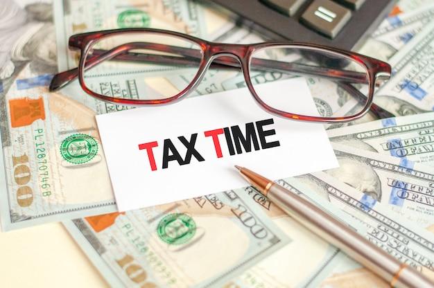 Op de tafel liggen rekeningen, een bundel dollars en een bord waarop het staat geschreven - belastingtijd. bedrijfs- en financieel concept.