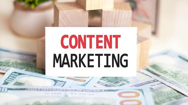 Op de tafel liggen rekeningen, een bundel dollars en een bord waarop het staat geschreven - content marketing. financiën en economie concept.
