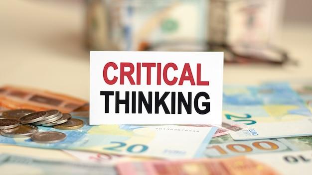 Op de tafel liggen rekeningen, een bundel dollars en een bord waarop het staat geschreven - kritisch denken. financiën en economie concept.