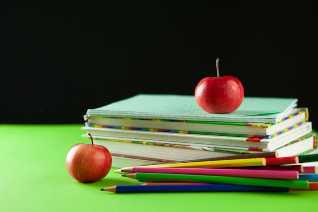 Op de tafel liggen schoolboeken, boeken, tetra's, kleurpotloden en een rode appel - een symbool van terug naar school. terug naar school-concept.