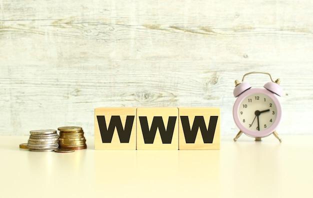 Op de tafel naast de munten liggen drie houten kubussen met letters. het woord www. op een grijze achtergrond.