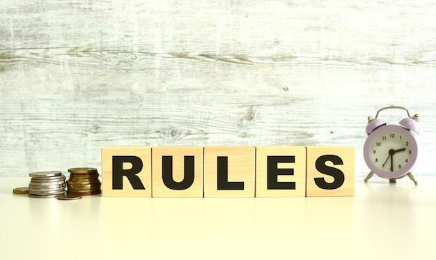 Op de tafel naast de munten liggen vijf houten kubussen met letters. regels woord. op een grijze achtergrond.