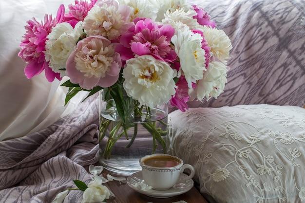 Op de tafel staat een kopje koffie en een boeket pioenrozen
