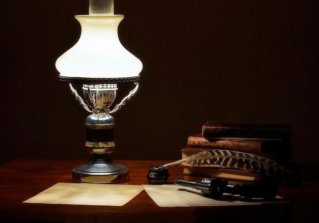 Op de tafel staat een lamp oude boeken en een pen met een inktpotje