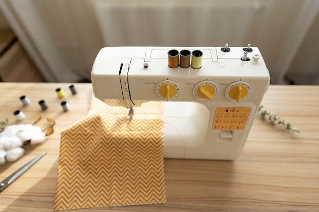 Op de tafel staat een witte naaimachine