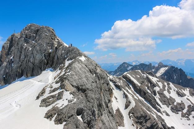 Op de top van dachstein en uitzicht alpiene bergen. nationaal park in oostenrijk, europa. blauwe en bewolkte hemel in de zomerdag