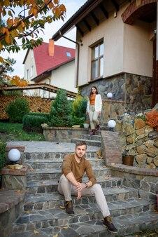 Op de trappen van hun huis zitten een man en een vrouw. focus op de man.