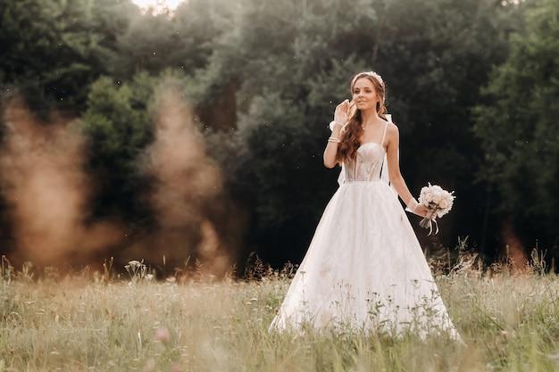 Op de trouwdag staat een elegante bruid in een witte lange jurk en handschoenen met een boeket in haar handen op een open plek te genieten van de natuur