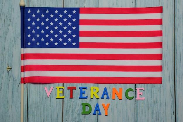 Op de vlag van de vs is de tekst veterance day bekleed met veelkleurige letters op een achtergrond