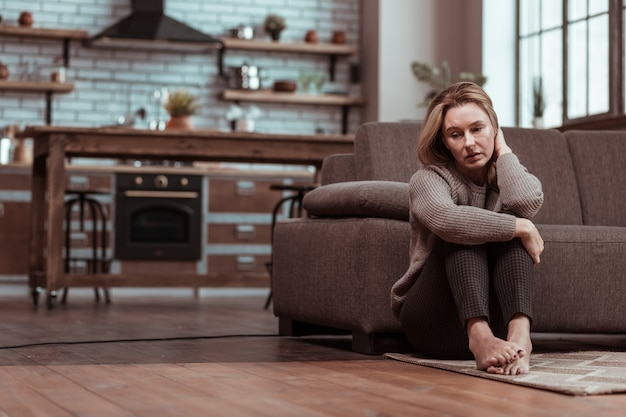 Op de vloer. depressieve rijpe vrouw die op de grond zit terwijl ze zich gestrest voelt na een familieruzie