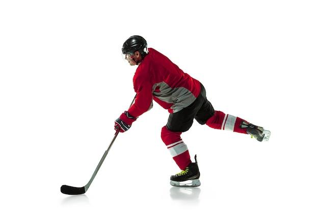 Op de vlucht. mannelijke hockeyspeler met de stok op ijsbaan en witte muur. sportman uitrusting dragen en helm oefenen. concept van sport, gezonde levensstijl, beweging, beweging, actie.